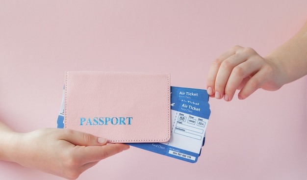 Close up horizontal féminin touristique en main billets d'avion avec passeport orange, carte d'embarquement, isolé sur jaune