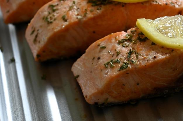 Close up horizontal de filets de saumon avec des feuilles de citron et de persil sur une plaque à pâtisserie