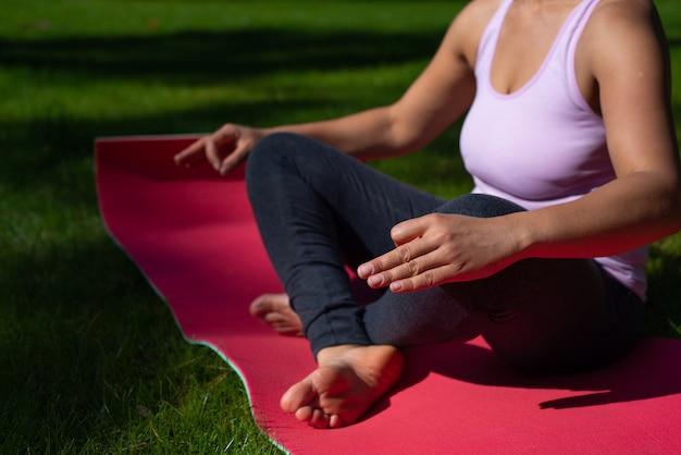 Close up image de la méditation dans le parc sur un tapis de fitness rose