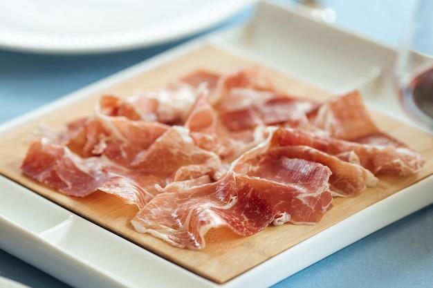Close-up de jambon de porc tranché espagnol sur la plaque blanche