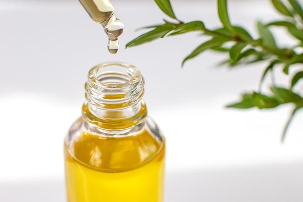 Close up jaune goutte d'huile essentielle ou biologique dans une pipette en verre sur une bouteille