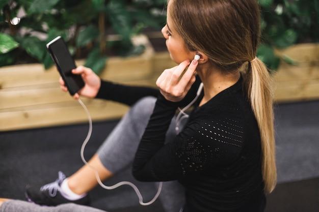 Close-up d'une jeune femme écoutant de la musique dans la salle de gym