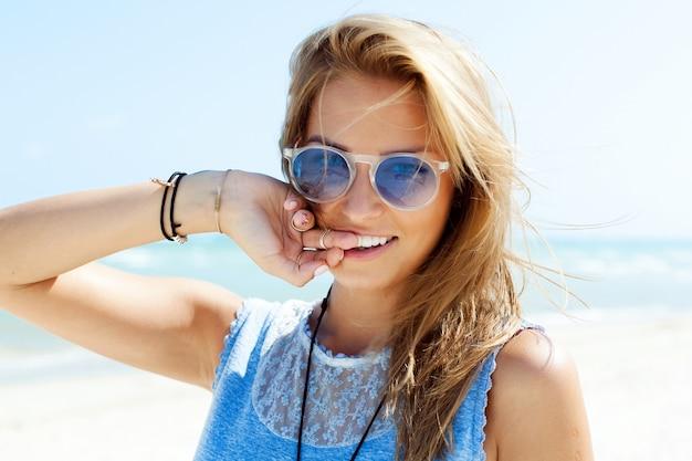 Close-up d'une jeune fille avec un grand sourire sur la plage