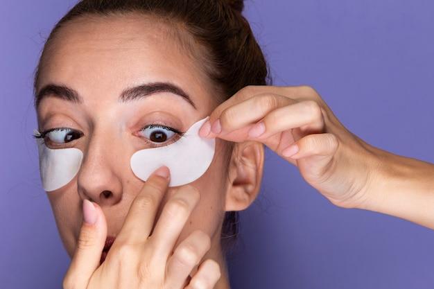 Close-up jeune fille avec des tampons pour les yeux