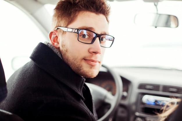Close-up d'un jeune homme avec des lunettes assis dans la voiture