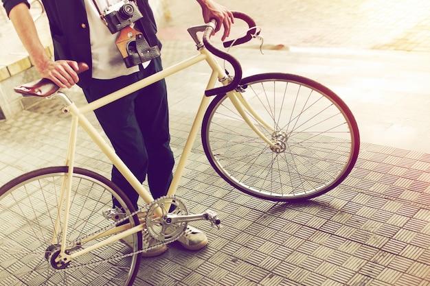 Close-up d'un jeune homme avec vélo vintage et appareil photo