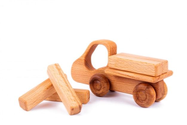 Close-up jouet pour enfants en bois naturel sous forme de camion à benne basculante avec des blocs de bois en forme de cargaison sur blanc