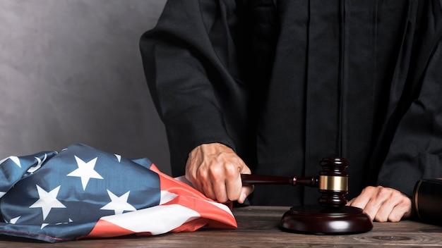 Close-up juge avec drapeau frappant le marteau