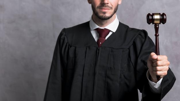 Close-up juge en robe tenant marteau