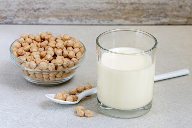 Close up de lait de pois chiche végétalien dans un petit verre à boire avec des haricots