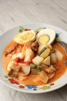 Close up lontong sayur padang, curry de légumes avec gâteau de riz pressé (lontong), servi avec egguf à la coque sur table en bois
