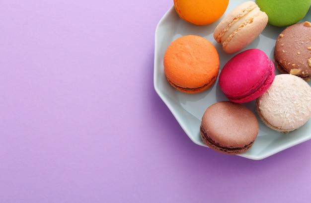Close up de macarons français colorés sur plaque bleue