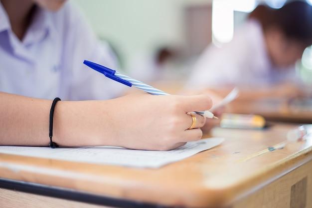 Close-up main d'étudiants écrivant un examen en salle de classe avec le stress