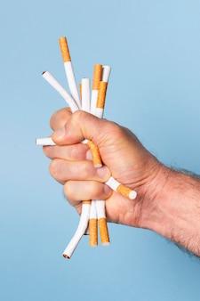 Close-up main serrant les cigarettes