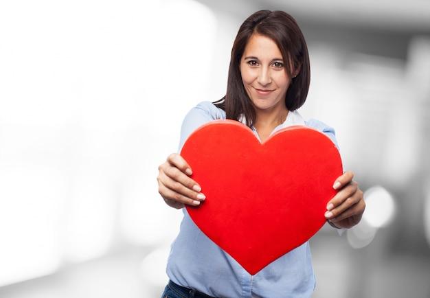 Close-up des mains de femme d'affaires tenant un coeur rouge