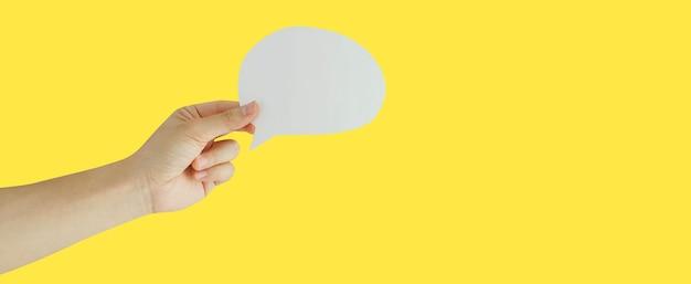 Close up man hand hold discours bulle papier coupé isolé n fond jaune pour le concept de design
