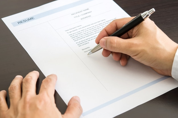 Close-up man signant sur le formulaire de résumé.