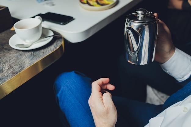 Close up man verser le thé chaud de la théière dans un petit verre près de la fenêtre