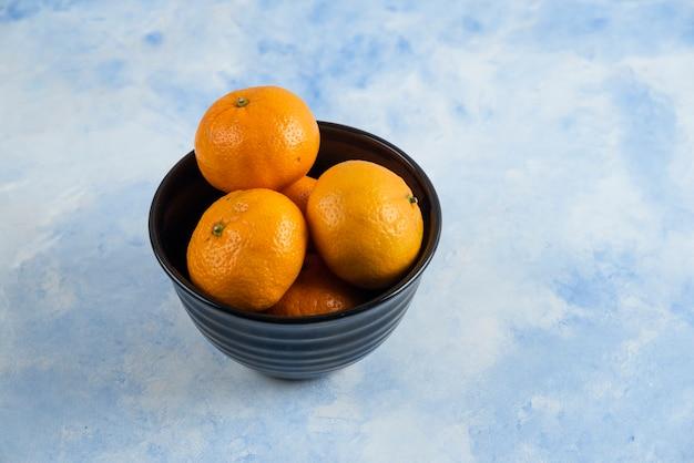 Close up de mandarines clémentines dans un bol noir