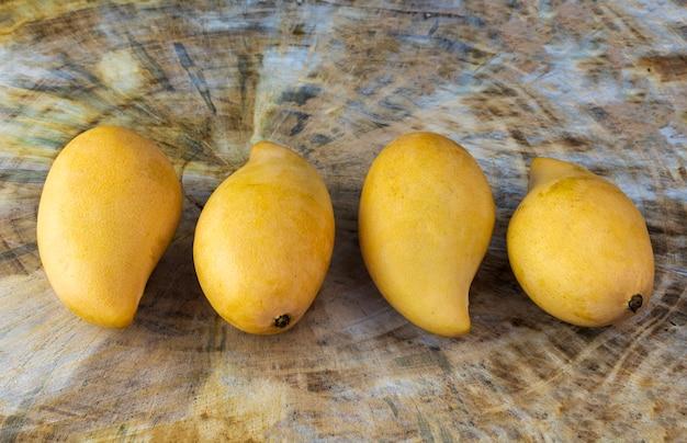 Close up mangues fraîches jaunes sur table en bois véritable. fruits tropicaux de mangue. 4 mangues.