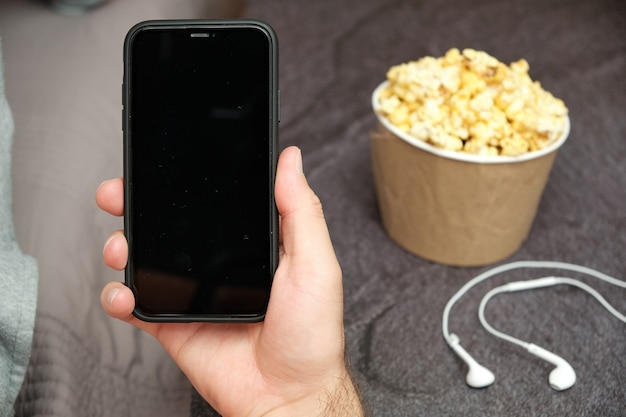Close up mans hand holding a mobile phone avec copie espace avec écouteurs et boîte de pop-corn à côté de lui