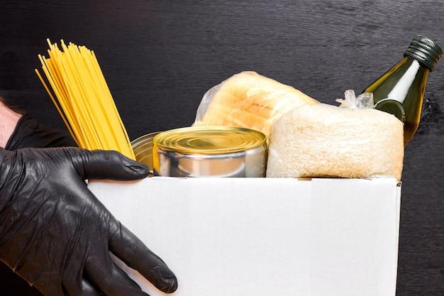 Close up mans mains dans des gants en caoutchouc noir tenant une boîte blanche avec des pâtes, des céréales et des aliments en conserve sur un mur noir. service de livraison de nourriture de sécurité.