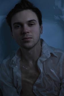 Close-up mode portrait d'un bel homme mal rasé caucasien sous l'eau en chemise blanche mouillée sexy regardant le visage fort de la caméra