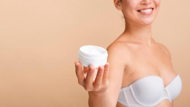 Close-up modèle heureux avec pot de crème et soutien-gorge blanc