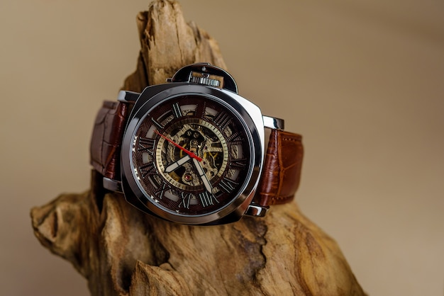 Close up de montres-bracelets homme de luxe placés sur du bois dans un mur marron