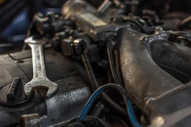 Close-up de moteur sale de voiture démontée aux pièces de moteur au garage de voiture