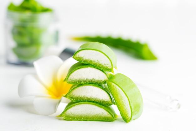 Close-up naturel d'aloe vera biologique en tranches pour liquide cosmétique fait maison contre du blanc.