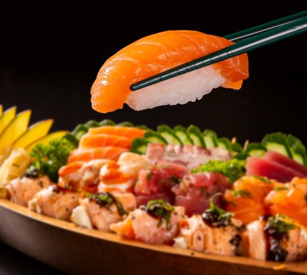 Close up nigiri saumon à hashi avec combo de nourriture japonaise défocalisé en fond noir.
