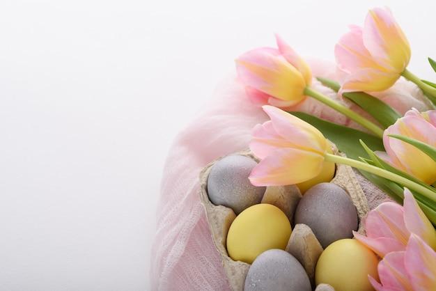 Close-up d'oeufs de pâques bleu et jaune pastel avec des tulipes roses avec serviette en tissu rose sur fond blanc, concept de pâques