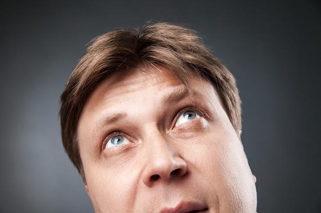 Close-up of adult man recherchant avec curiosité sur fond noir