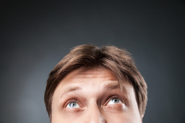 Close-up of adult man scrutant et levant.studio shot