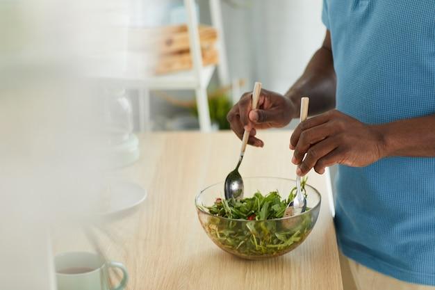 Close-up of african young man cooking salade de légumes frais tout en se tenant près de la table dans la cuisine
