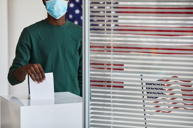 Close-up of afro-american man in mask mettant le bulletin de vote dans l'urne au bureau de vote pendant la pandémie