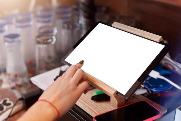 Close up of barista doigt avec manucure scrolling tablet pc au café