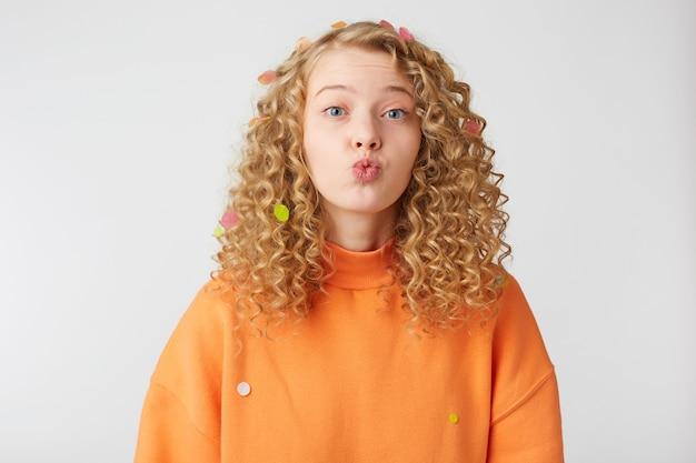 Close up of beautiful sweet nice blonde girl envoi de l'air baiser directement à l'avant avec un regard tendre, isolé sur un mur de studio blanc