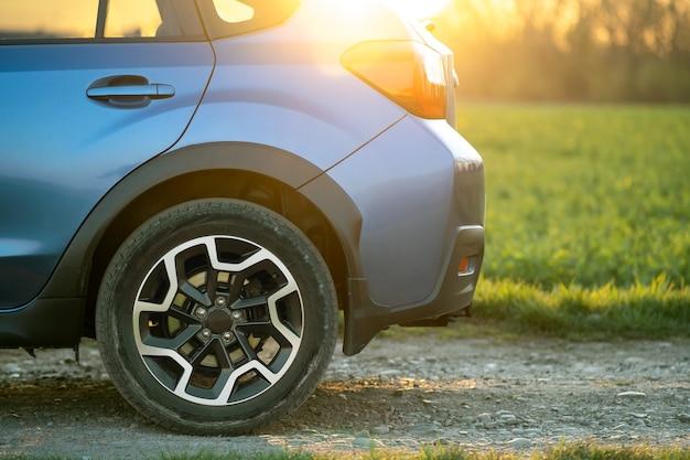 Close up of blue roue de voiture hors route sur route de gravier