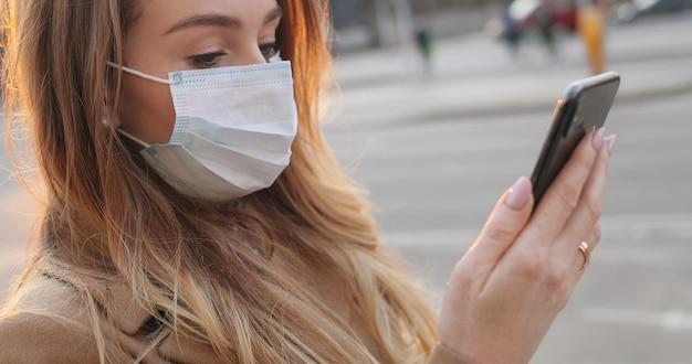 Close up of caucasian young woman in medical mask textos message et tapant sur téléphone mobile dans la rue. fille en tapant et en faisant défiler sur smartphone dans une ville vide en plein air. concept de pandémie.