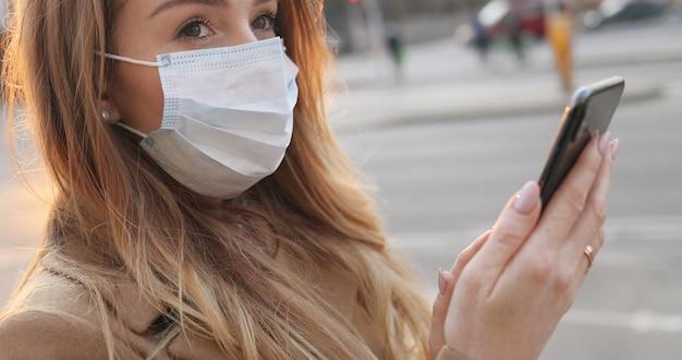 Close up of caucasian young woman in medical mask textos message et tapant sur téléphone mobile dans la rue. vue latérale sur la fille en tapant et en discutant avec des sms sur smartphone en ville à l'extérieur. concept de virus