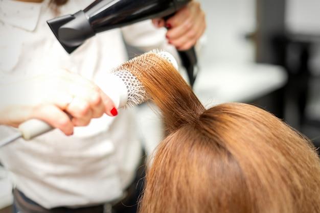 Close up of coiffeur séchant de longs cheveux rouges avec un sèche-cheveux et une brosse ronde dans un salon de beauté