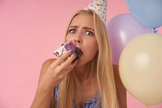 Close-up of confus jeune femme blonde aux cheveux longs en chapeau de cône de vacances manger un gâteau d'anniversaire sur des ballons à air multicolores, regardant la caméra et fronçant les sourcils