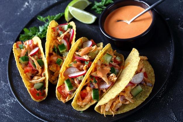 Close-up of corn taco coquilles chargées de poitrine de poulet râpée, légumes verts frais et légumes sur une plaque noire avec sauce au citron vert et buffle
