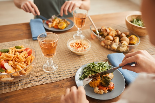 Close-up of couple mangeant un dîner sain et boire du vin à la table à la maison