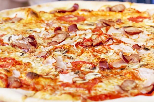 Close-up of delicious fresh pizza aux champignons, saucisses bavaroises et jambon