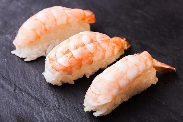 Close-up of ebi sushi avec crevettes sur fond d'ardoise noire