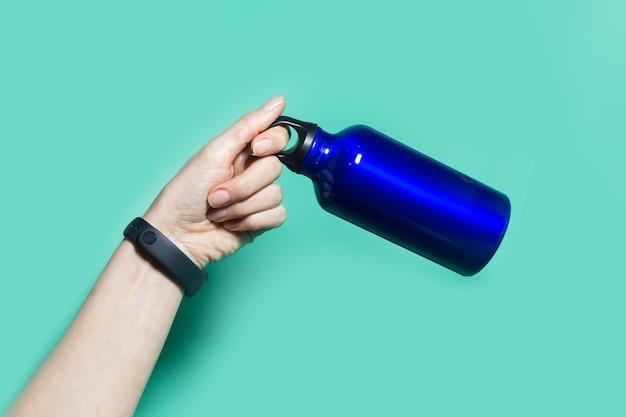 Close-up of female hand holding a réutilisable eco, bouteille d'eau thermo en acier de couleur bleu fantôme, isolé sur aqua menthe