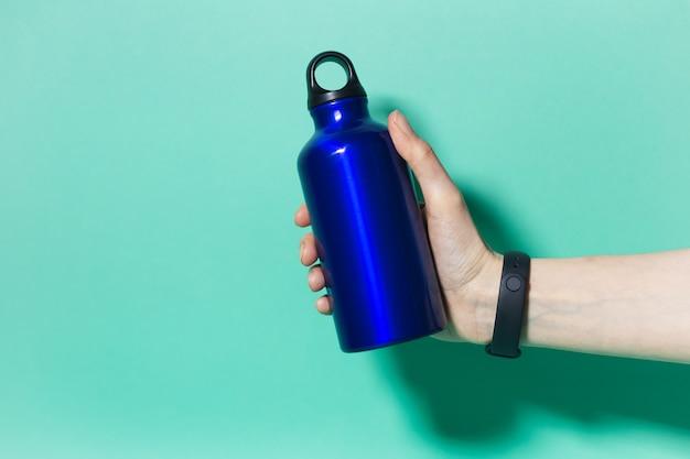 Close-up of female hand holding a réutilisable eco, bouteille d'eau thermo en aluminium de couleur bleu fantôme, isolé sur aqua menthe